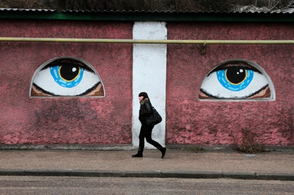 A woman walks past a building decorated with eyes in Crimean city of Sevastopol